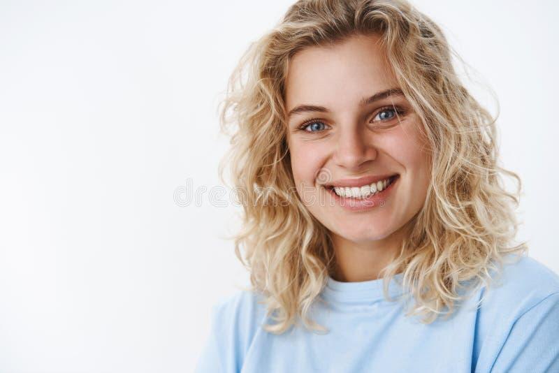 Fille avec le sourire sincère mignon riant et ayant l'amusement regardant amical et avec plaisir la caméra avec les yeux bleus pr photographie stock