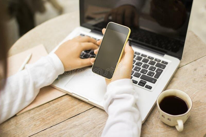 Fille avec le téléphone portable, l'ordinateur portable et la tasse de café vides photographie stock