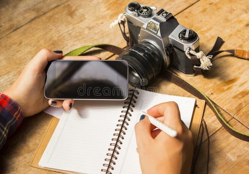 Fille avec le téléphone portable vide, le journal intime et le vieil appareil-photo image libre de droits