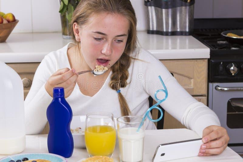 Fille avec le téléphone prenant le petit déjeuner dans la cuisine photographie stock libre de droits