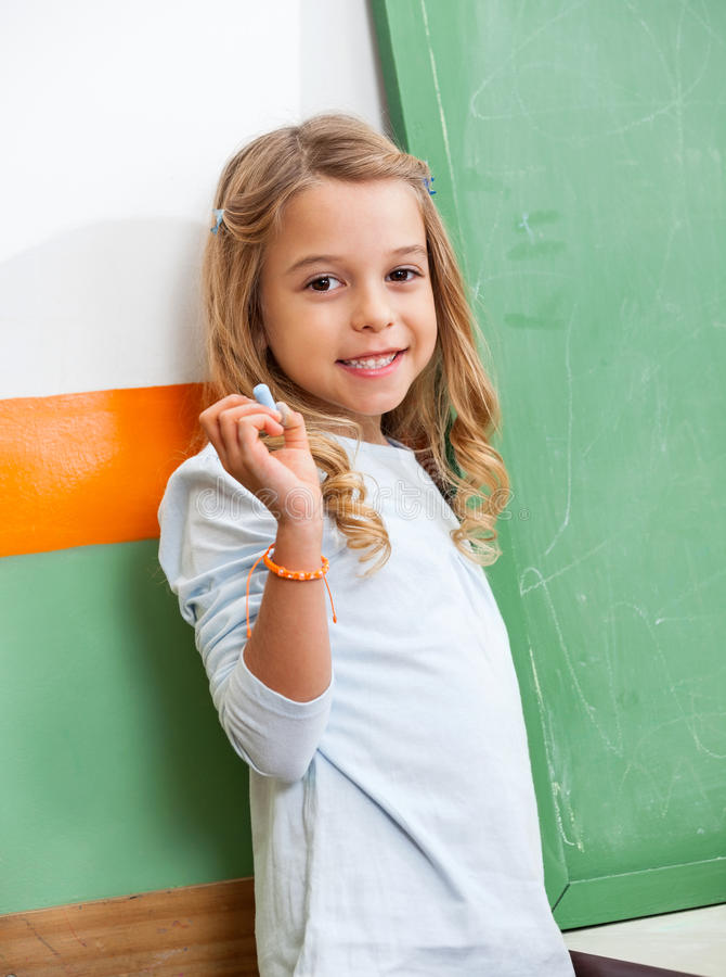 Fille avec le tableau se tenant prêt de craie dans la classe images stock