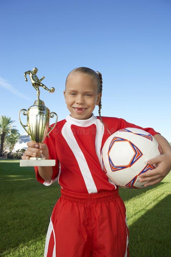 Fille avec le trophée et le ballon de football image stock