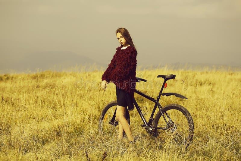 Fille avec le vélo sur la montagne images libres de droits