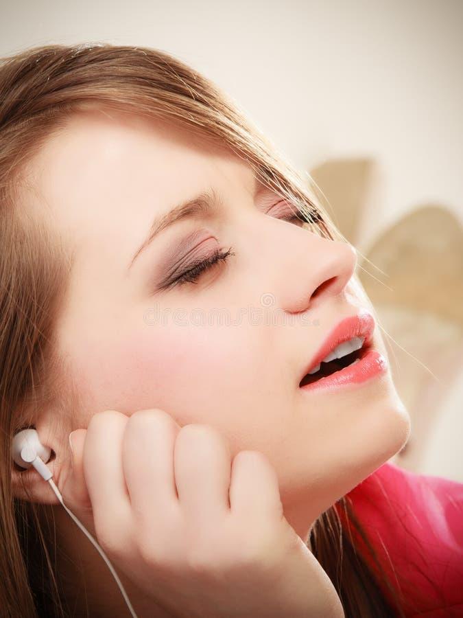 Fille avec les écouteurs blancs écoutant la musique image libre de droits