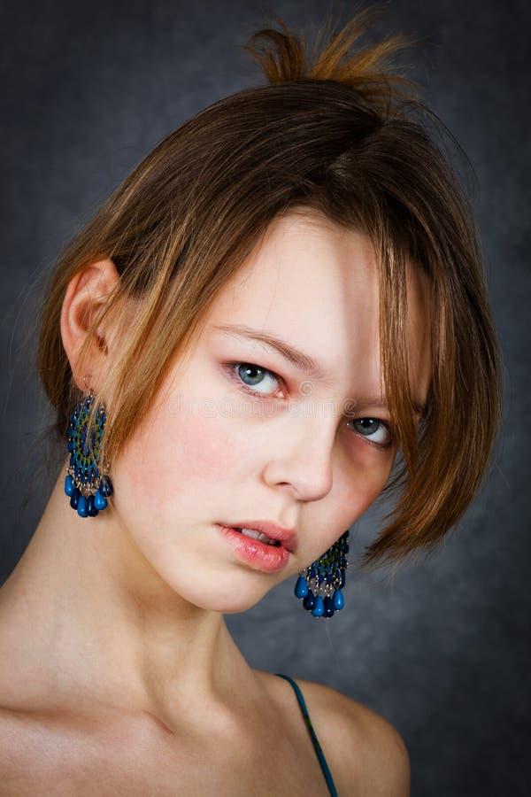 Fille avec les boucles d'oreille bleues image stock
