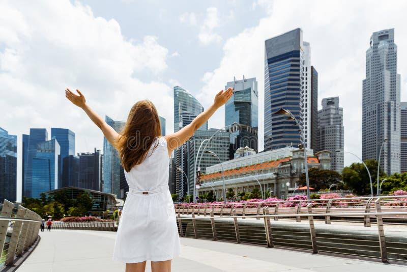 Fille avec les bras augmentés sur le fond de gratte-ciel photographie stock