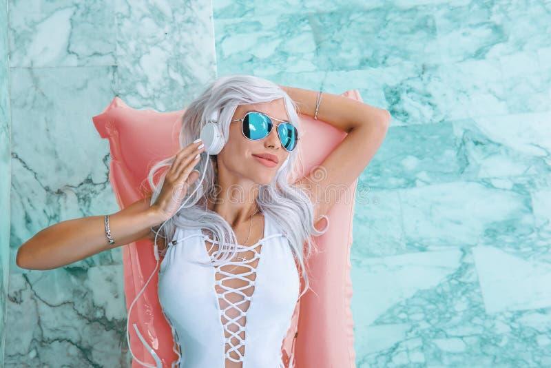 Fille avec les cheveux blancs dans des écouteurs écoutant la musique sur le flotteur rose de piscine photos stock