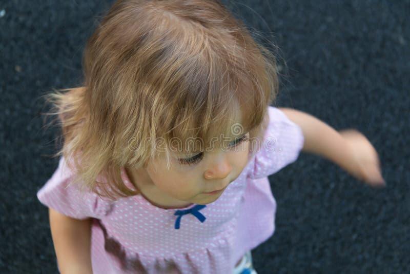 Fille avec les cheveux blonds tournant dans la robe rose sur l'asphalte Vacances d'été, amusement, joie, concept d'aventure Vue s images stock