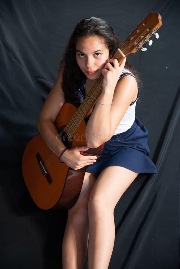 Fille avec les cheveux bruns, séance, alors que le sourire montre sa guitare tandis qu'elle joue Amused regardant l'appareil-phot photographie stock libre de droits