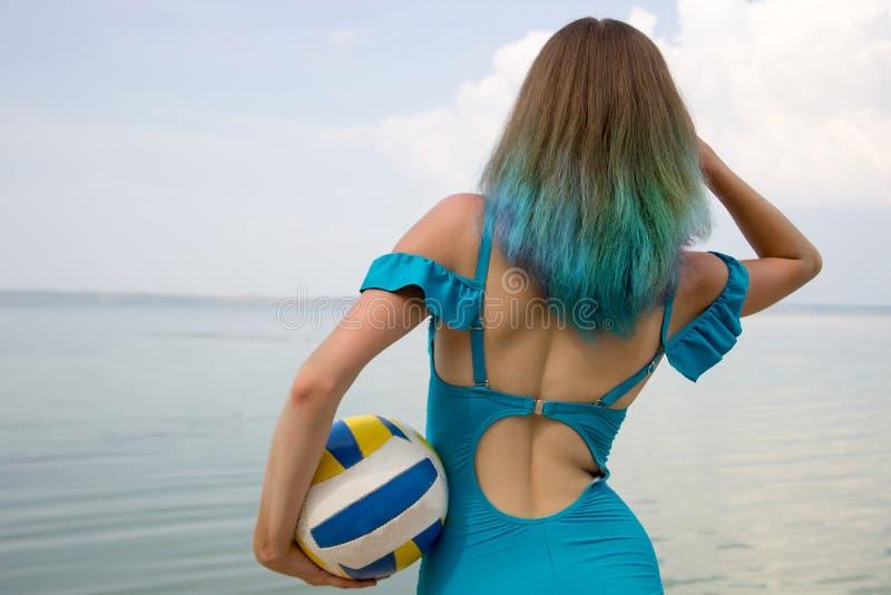 Fille avec les cheveux colorés dans un maillot de bain avec une boule de volleyball, sta photo stock