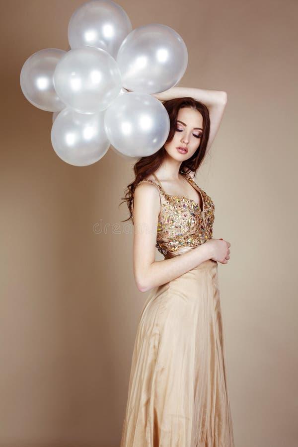 Fille avec les cheveux foncés portant la robe luxueuse, tenant les ballons blancs image stock