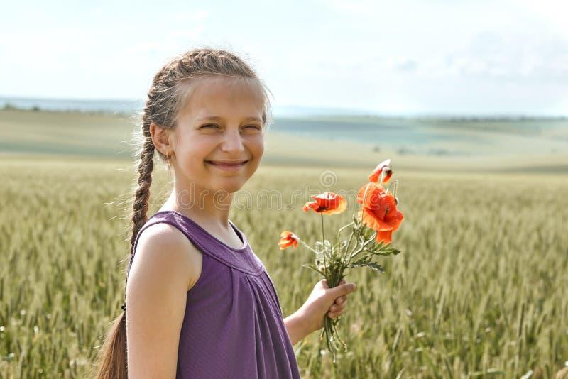 Fille avec les fleurs rouges de tulipe posant dans le domaine de blé, le soleil lumineux, beau paysage d'été images libres de droits