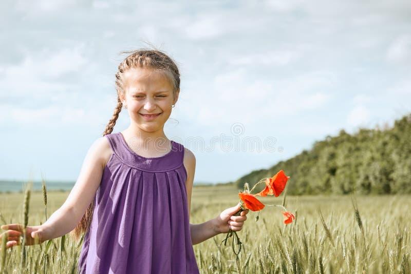 Fille avec les fleurs rouges de tulipe posant dans le domaine de bl?, le soleil lumineux, beau paysage d'?t? image stock