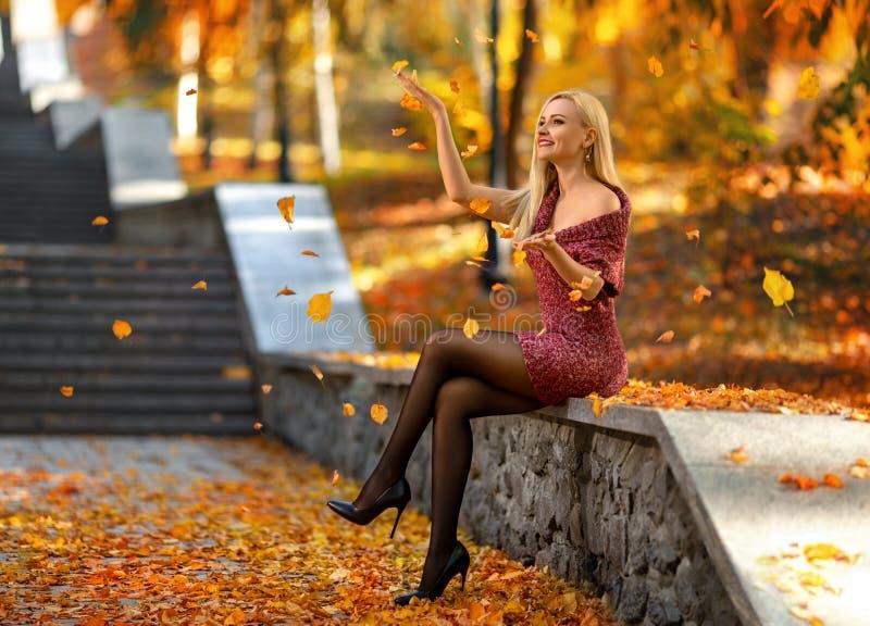 Fille avec les jambes parfaites jouant avec les feuilles tombées images libres de droits