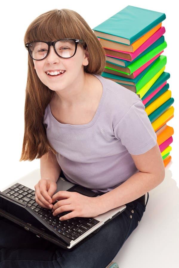 Fille avec les livres et l'ordinateur portatif de couleur photos libres de droits