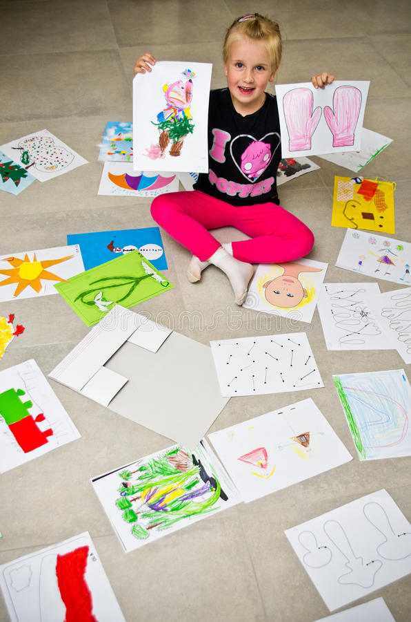 Fille avec ses dessins sur le plancher image stock