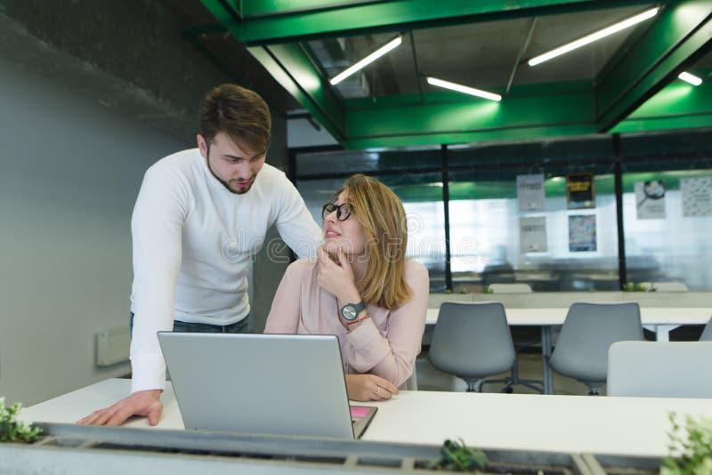 fille avec son mari au sujet du bureau près de l'ordinateur portable discuter le projet Les employés de bureau communiquent photo stock
