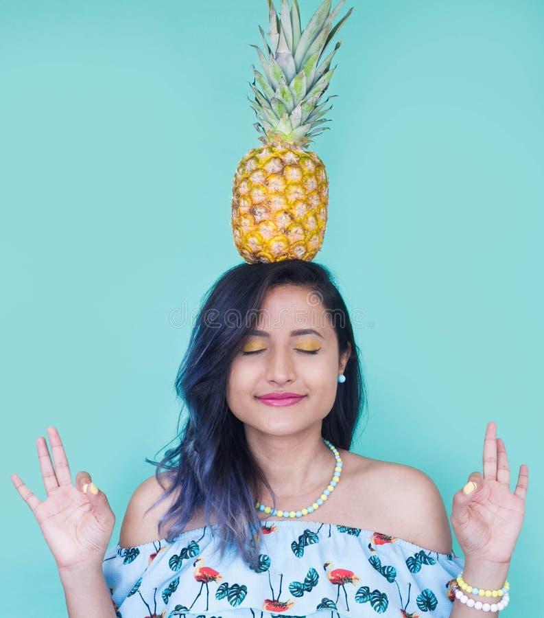 Fille avec un ananas sur sa tête Maquillage jaune et clous photographie stock