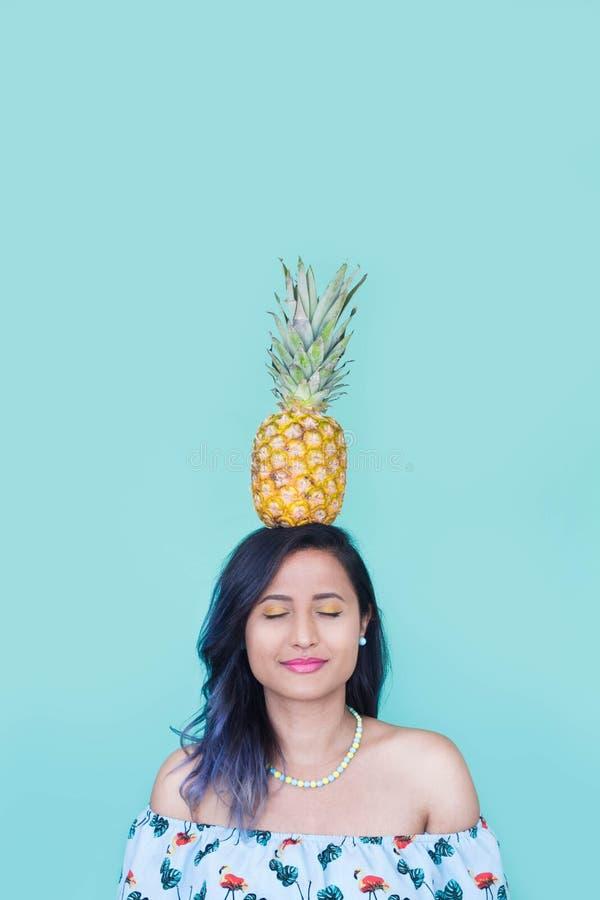 Fille avec un ananas sur sa tête Maquillage jaune et clous photos stock