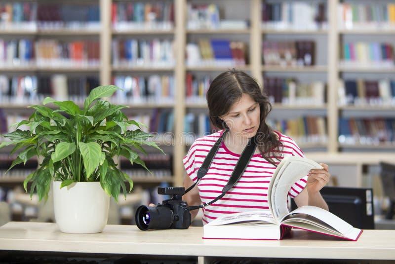 Fille avec un appareil-photo dans la bibliothèque lisant un grand livre photo stock