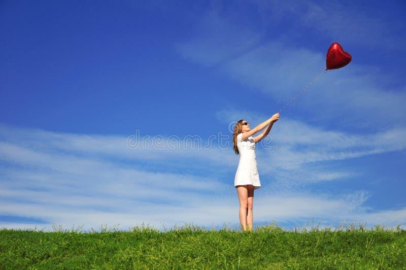 Fille Avec Un Ballon Rouge Sous Forme De Coeur Photographie stock libre de droits