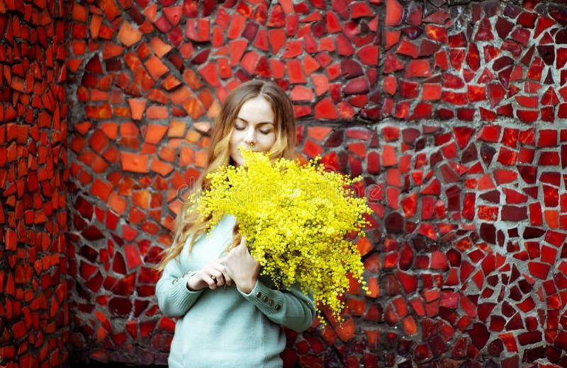 fille avec un bouquet des fleurs jaunes de la mimosa dans des ses mains photo stock
