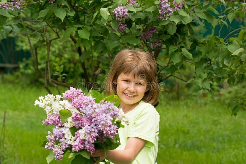 Fille avec un bouquet des lilas image stock