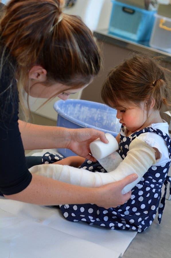 Fille avec un bras cassé image stock