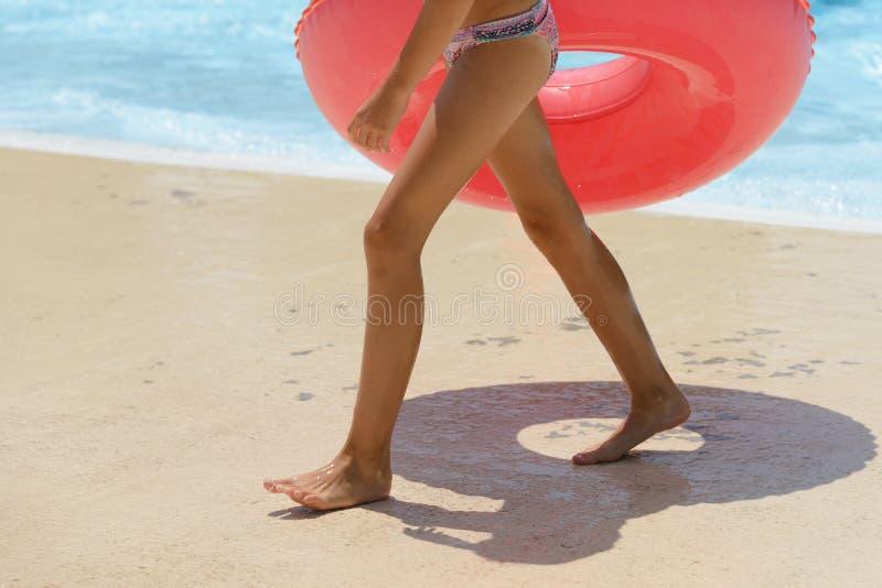 Fille avec un cercle gonflable sur la plage photographie stock libre de droits