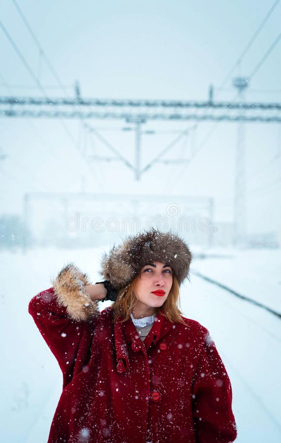 Fille avec un chapeau de fourrure posant dans la neige images stock