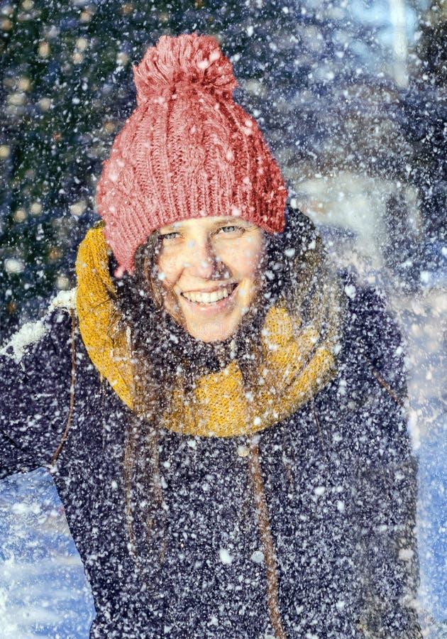 Fille avec un chapeau rouge dans une chute de neige image libre de droits