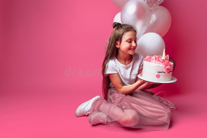 Fille avec un gâteau pour un anniversaire, dans le studio sur un fond rose, humeur de fête photographie stock libre de droits