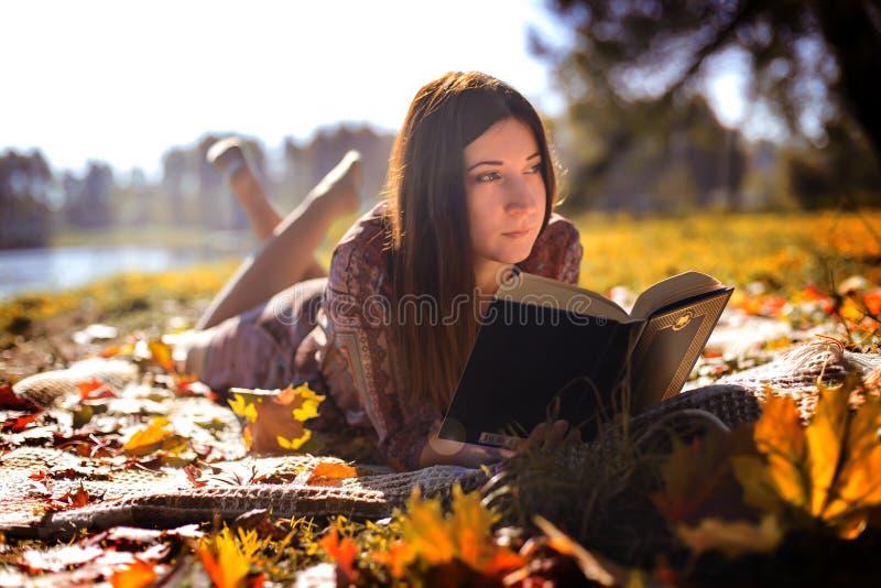 Fille avec un livre dans le feuillage d'automne photos stock