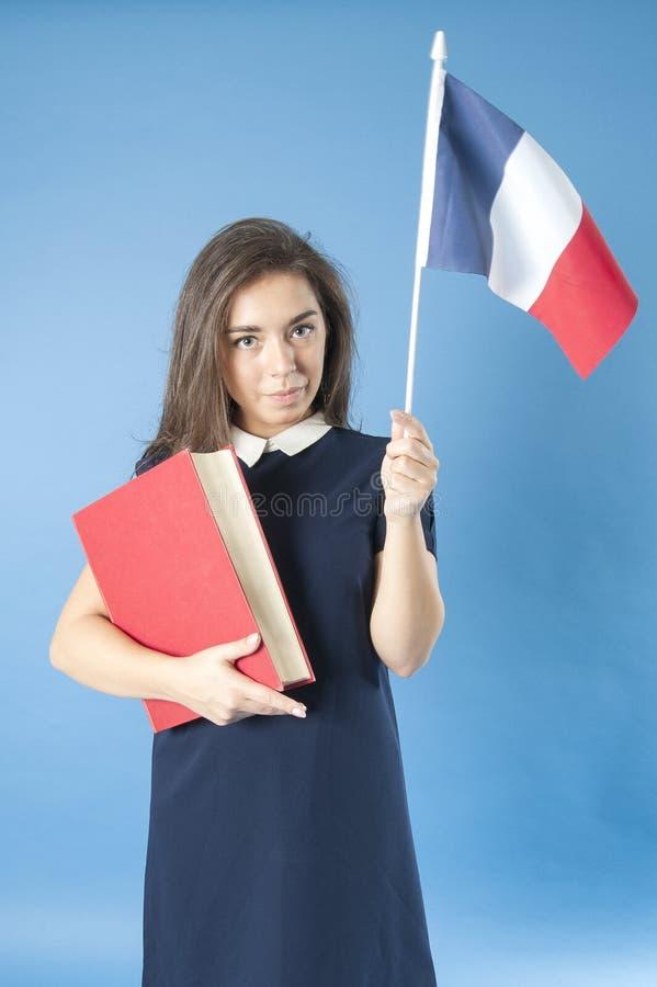 Fille avec un livre et un drapeau français photographie stock libre de droits
