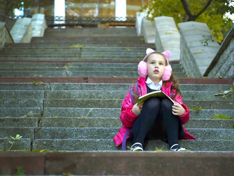 Fille avec un livre se reposant sur les étapes photographie stock libre de droits