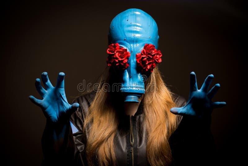 Fille avec un masque de gaz sur un fond gris photographie stock