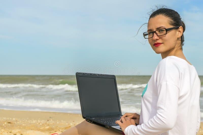 Fille avec un ordinateur portable travaillant à la plage de mer photographie stock libre de droits