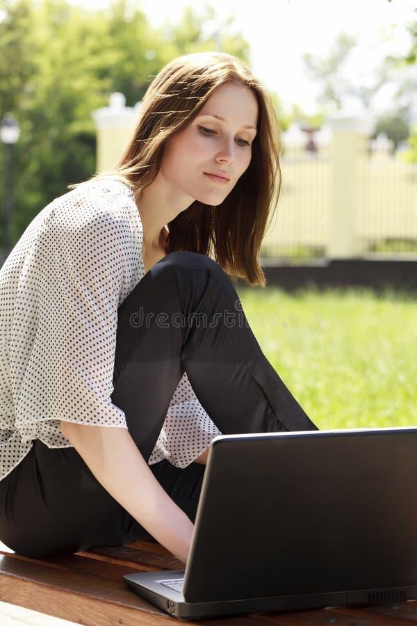 Fille avec un ordinateur portatif au stationnement image stock