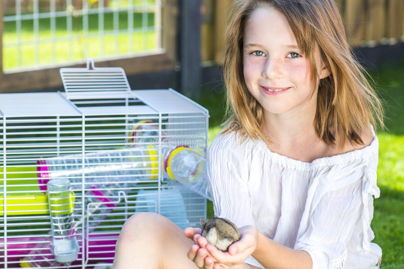 Fille avec un petit hamster dans des paumes photos stock