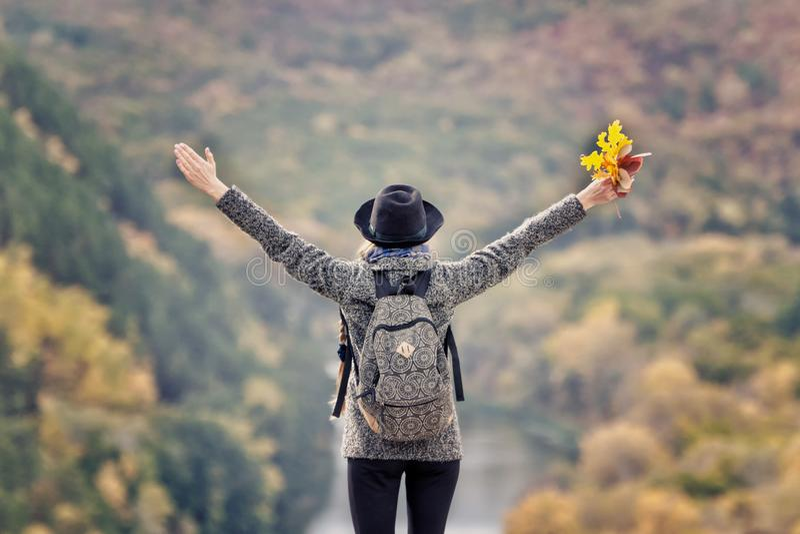 Fille avec un sac à dos et un chapeau se tenant sur une colline Les mains ont augmenté vers le haut Rivière et montagnes ci-desso image libre de droits