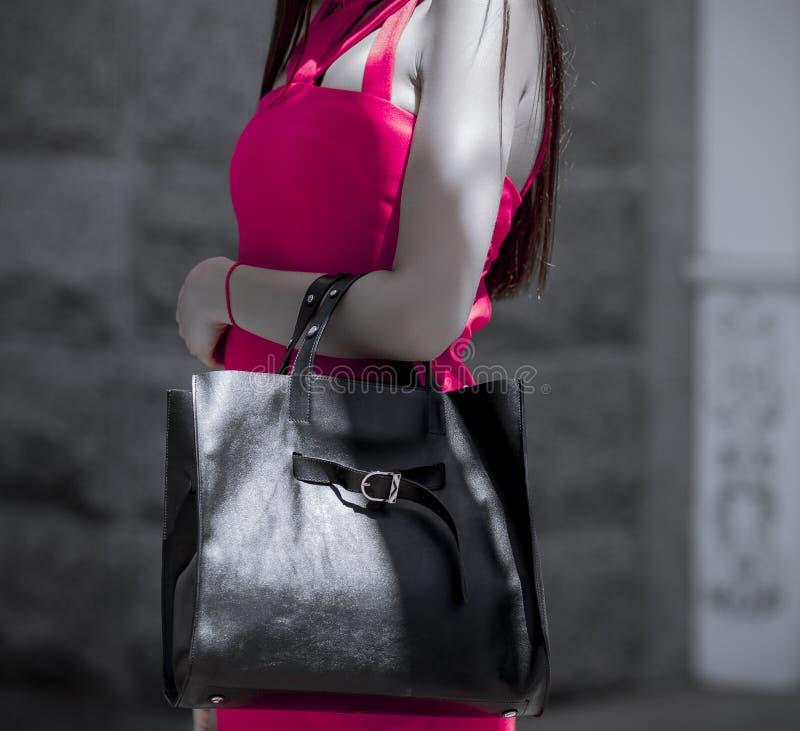 Fille avec un sac dans une robe convenable rose images stock
