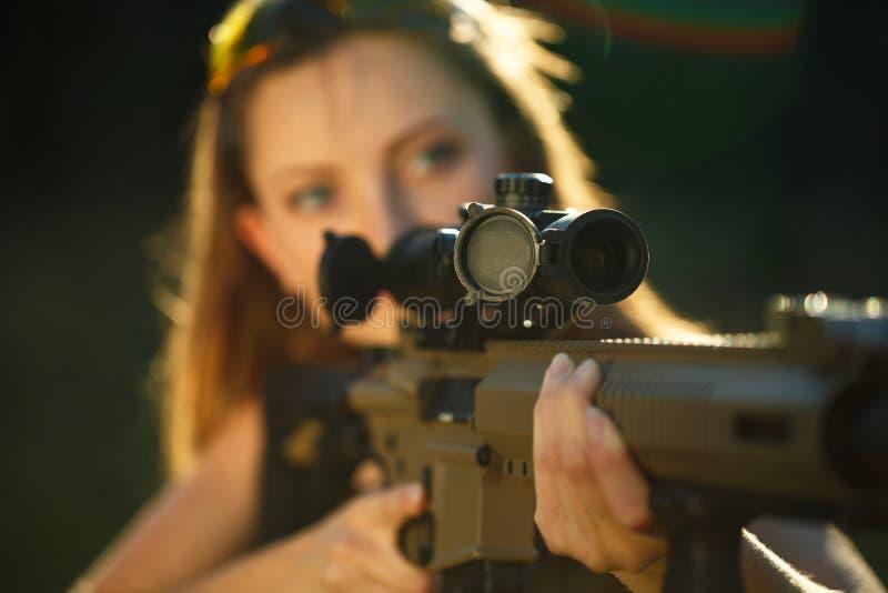 Fille avec une arme à feu pour le tir de piège visant une cible photo libre de droits