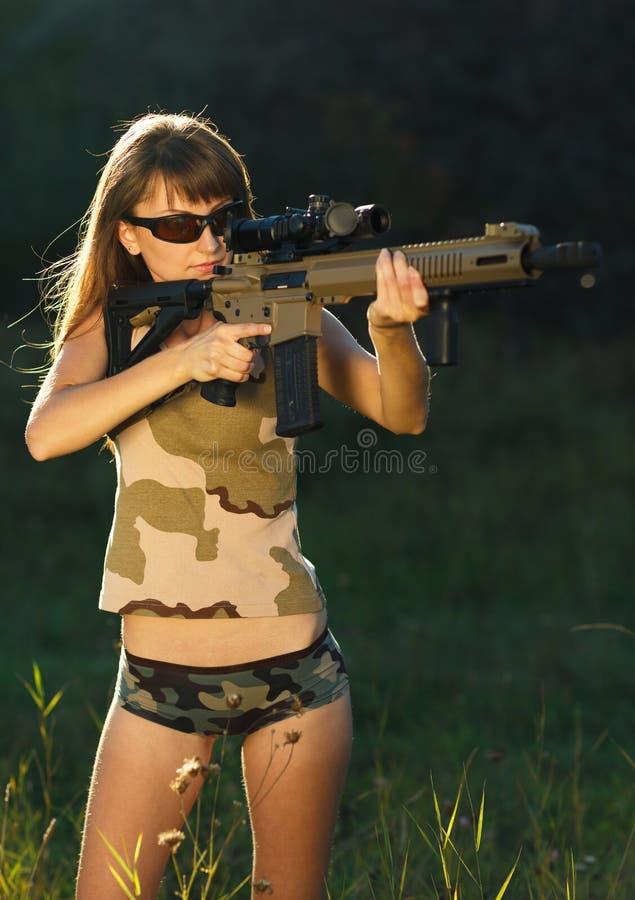 Fille avec une arme à feu pour viser de tir de piège et en verre de tir image libre de droits