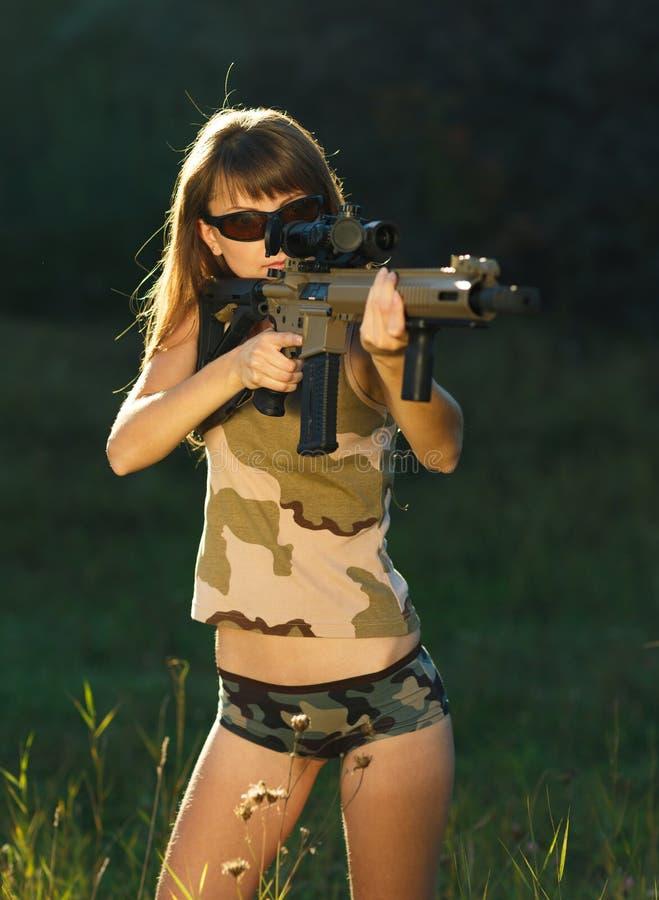 Fille avec une arme à feu pour viser de tir de piège et en verre de tir photos libres de droits