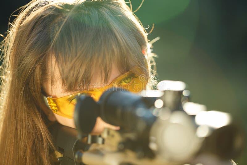 Fille avec une arme à feu pour viser de tir de piège et en verre de tir images stock