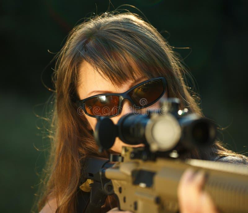 Fille avec une arme à feu pour viser de tir de piège et en verre de tir images libres de droits