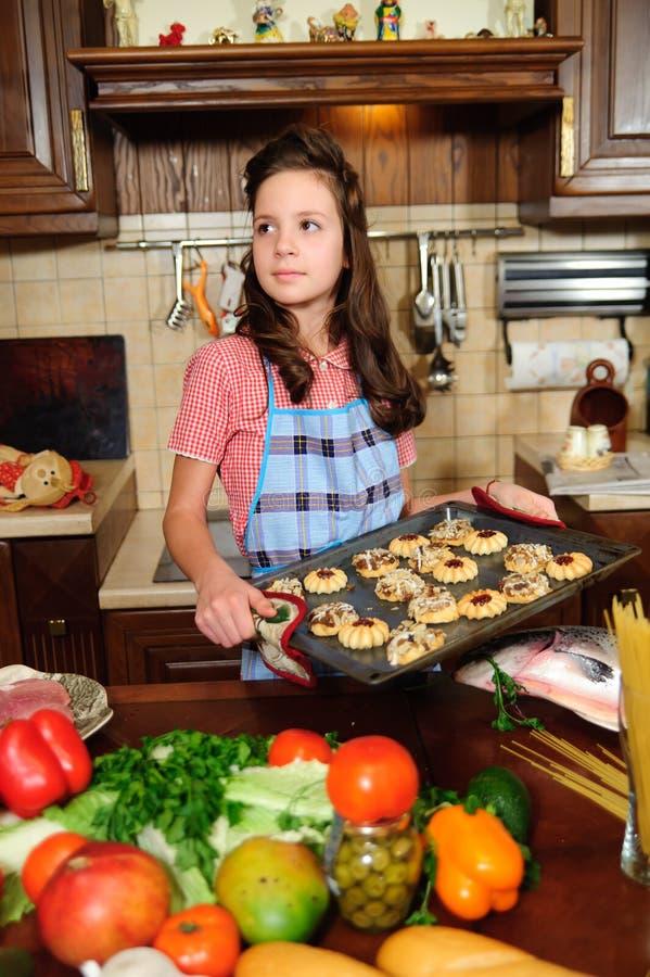 Fille avec une coupe de cheveux vintage dans la cuisine parmi les légumes avec un plateau avec des biscuits cuits au four photos stock