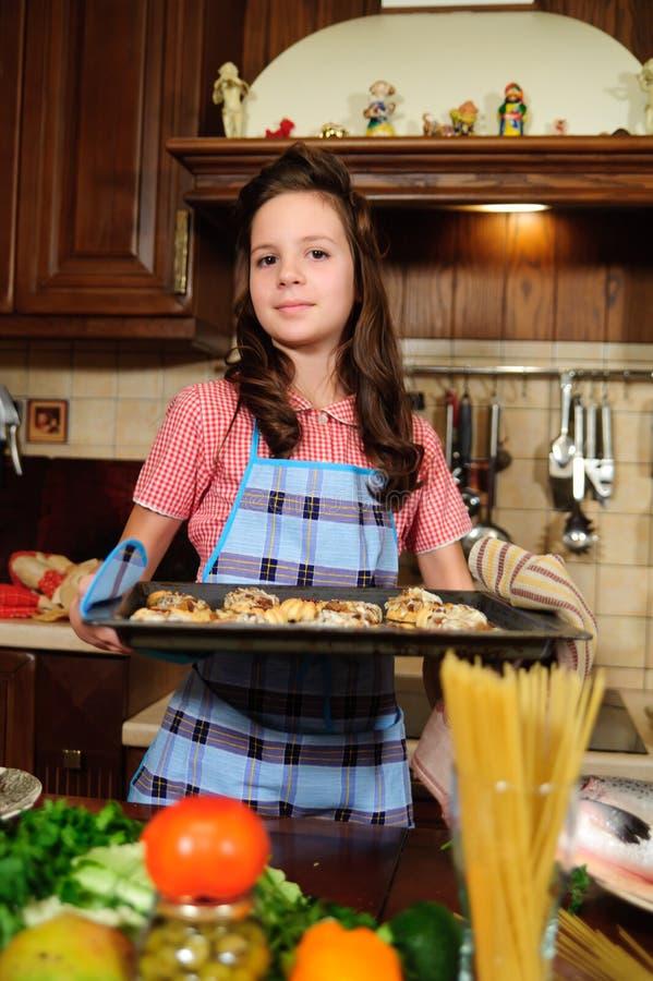 Fille avec une coupe de cheveux vintage dans la cuisine parmi les légumes avec un plateau avec des biscuits cuits au four image stock