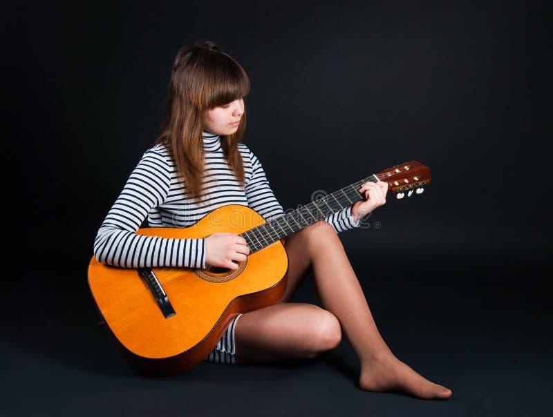 Fille avec une guitare sur un fond noir photographie stock libre de droits