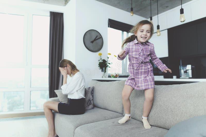 Fille ayant l'amusement sautant sur le sofa quand mère contrariée image stock